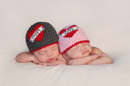 Foto de Five week old sleeping boy and girl fraternal twin newborn babies  They are wearing crocheted  Love Mom  and  Love Dad  beanies  - Imagen libre de derechos