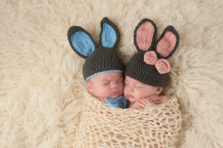 Photo pour Sleeping 2 month old newborn baby twins wearing bunny costumes. They are swaddled together in a hugging position. - image libre de droit