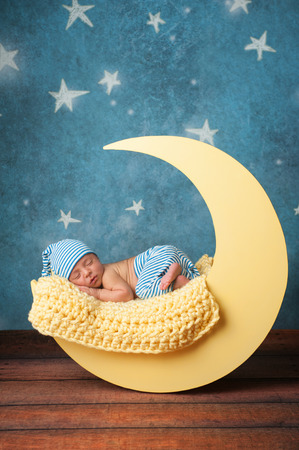 Studio portrait of a nine day old baby boy wearing pajama bottoms and a sleeping cap. He is sleeping on a moon shaped posing prop.