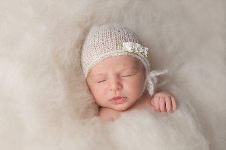 4a535c8af7f A portrait of a beautiful seven day old newborn baby girl wearing a white