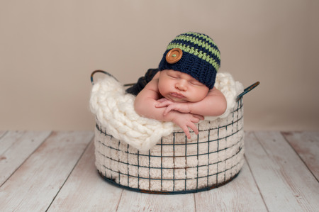 65fb6c657f3 Three week old newborn baby boy wearing jeans and a crocheted blue and  green beanie hat
