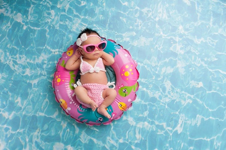 Nine day old newborn baby girl sleeping on a tiny inflatable swim ring. She is wearing a crocheted pink and white bikini and pink sunglasses.