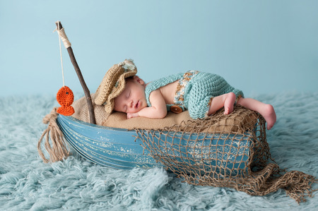 Photo pour Portrait of a three week old newborn baby boy. He is sleeping in a miniature boat and wearing crocheted overalls and a fisherman's hat. Shot in the studio on an aqua colored flokati rug. - image libre de droit