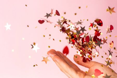 Photo pour Gold star confetti in women's hand on pastel pink background side view.Bright and festive holiday background. - image libre de droit