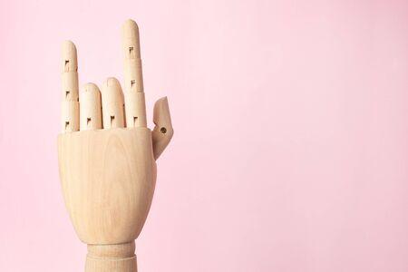 Foto de Wooden robot hand rock on pink background with copyspace side view - Imagen libre de derechos