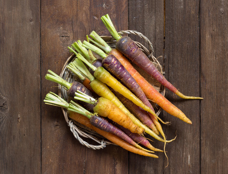 Fresh organic rainbow carrots on a wooden tableの写真素材