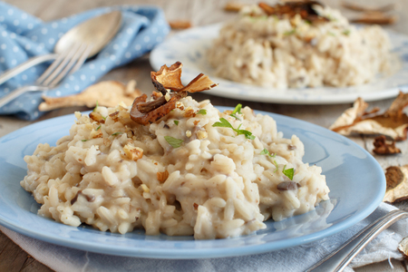 Foto de Risotto with porcini mushrooms on a blue plate on a wooden table - Imagen libre de derechos