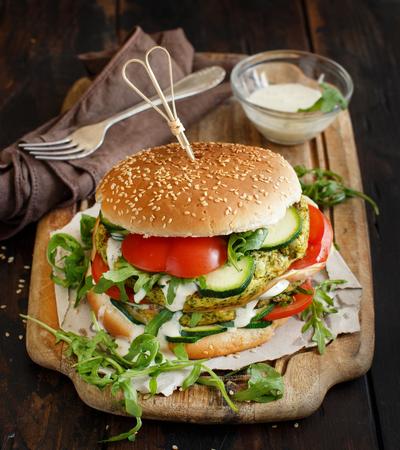 Foto de Healthy vegetarian burger with broccoli burger, arugula, zucchini and tomatoes - Imagen libre de derechos