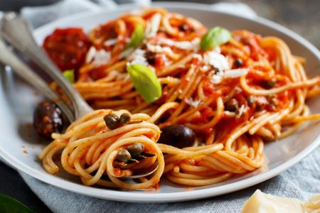 Photo pour Pasta alla puttanesca - Spaghetti with tomato sauce olives and capers - image libre de droit