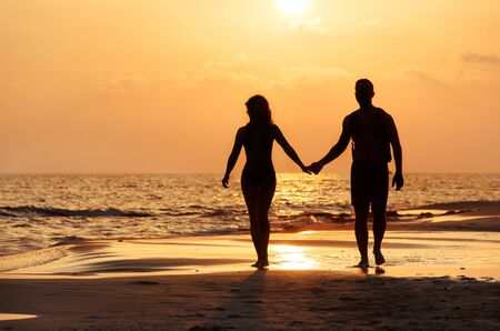 Photo pour Silhouette of a couple walking at the beach in front of the sunset  - image libre de droit