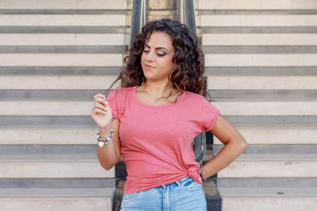 Photo for Young women wearing t-shirt and jeans stays near the stairs and touch hairs - Royalty Free Image
