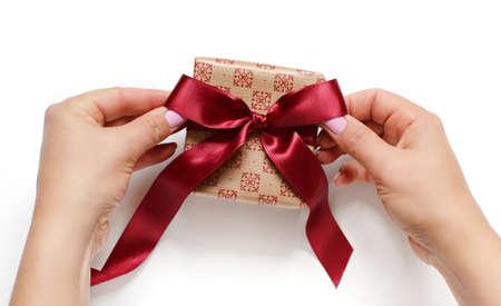 Photo pour Hands tie a ribbon bow on anEcru gift box on white top view - image libre de droit