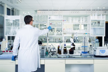 Foto de Interior of clean modern white medical or chemical laboratory background. Laboratory concept with caucasian male chemist. Horizontal template for a poster, webpage or leaflet. - Imagen libre de derechos