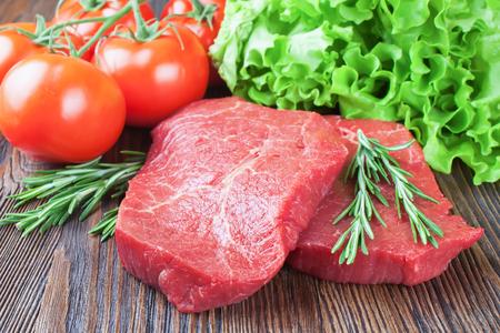 Foto für Fresh raw beef steak with spice and vegetable on brown wooden table - Lizenzfreies Bild
