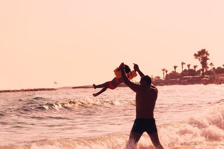 Happy Father and Child playing on the beach at the  Summer sunset time. Concept of friendly family.