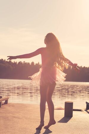 Photo pour Beautiful Teen Girl with long flowing curly hair is dancing  in the wind against the background of the sea. - image libre de droit