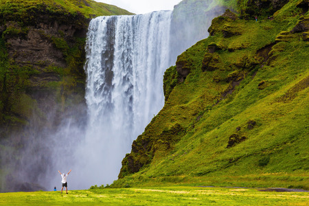 Photo pour Grand waterfall Skogafoss in Iceland. Tourist in shirt and bandana threw up his hands with delight the beauty of nature - image libre de droit