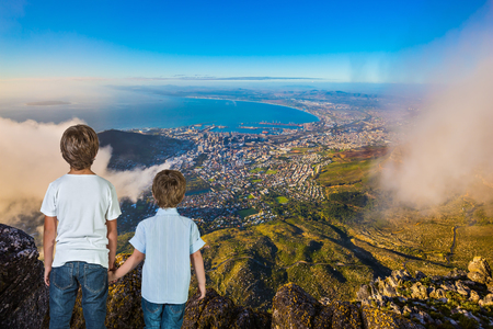 The concept of active tourism and recreation. Travel to Africa. Two boys standing on top of Table Mountain in the clouds