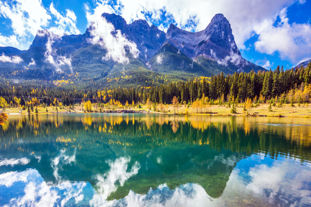 Photo pour Magnificent mountains Three Sisters  and scenic cumulus clouds are reflected in the water. Rocky Mountains, Canmore. The concept of recreational tourism - image libre de droit
