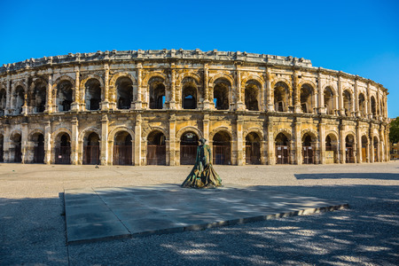 Roman arena in Nimes, Provence. Monument to bullfighter mounted on the square in front of the amphitheater. Photo taken fisheye lens