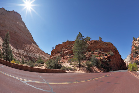 A bright sunny day in Zion National Park. Excellent road winds sharply between the picturesque hills of colorful striped sandstone