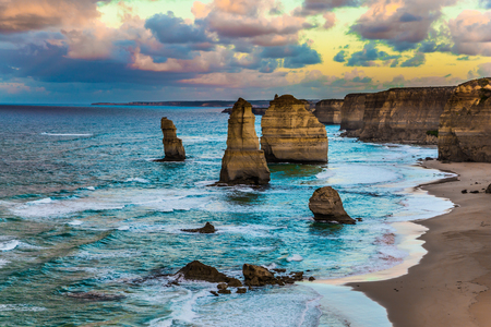 Travel to Australia. Early morning on the ocean shore. Pink dawn clouds over the famous rocks Twelve Apostles. The concept of active, ecological and photo tourism