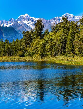 Photo pour Lake Matheson is glacial lake. South Island of New Zealand. Water reflects Mount Cook and Mount Tasman. Mountain peaks covered with snow. The concept of ecological, active and photo tourism - image libre de droit
