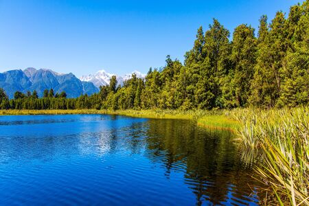 Photo pour The famous lake Matheson reflects Mount Cook and Mount Tasman. Lake Matheson is picturesque glacial lake in the South Island of New Zealand. The concept of ecological, active and photo tourism - image libre de droit