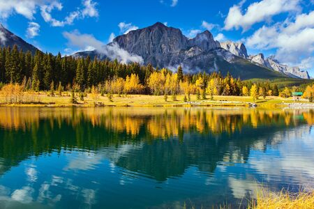Photo pour The Canadian Rockies. The city of Canmore in Banff Park. Bright autumn forest is reflected in the smooth water of the lake. The concept of active, ecological and photo tourism - image libre de droit