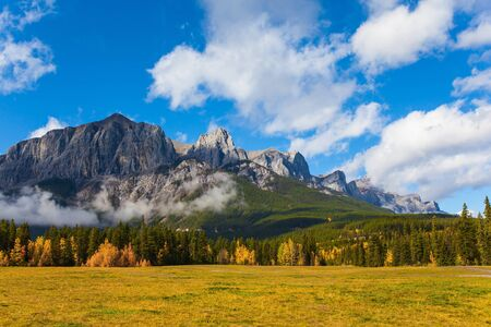 Photo pour Lush bright autumn day in the Canadian Rockies. The majestic Rocky Mountains. The Three Sisters Mountain is covered in lush white clouds. The concept of active, ecological and photo tourism - image libre de droit