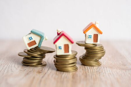 Photo pour Mini house model and stack of coins. House on a coin that is about to fall. Business risk management. Property investment and house mortgage financial real estate concept . - image libre de droit