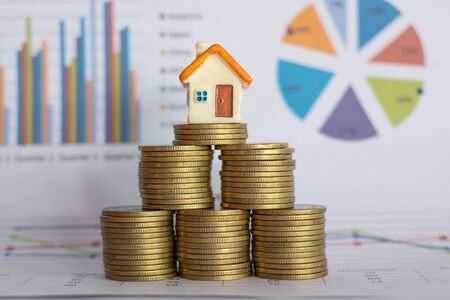 Photo pour A small house on a pile of coins And have a financial chart.Mini house model and stack of coins. Business growth. Property investment and house mortgage financial real estate concept - image libre de droit