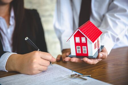 Businessmen and customers are signing home purchase agreements. Hand holding the pen signing purchase contract. Gray roof houses and keys placed close to each other.Real estate mortgage home purchase.