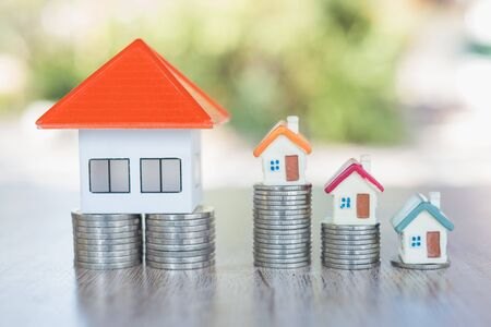 Photo pour Orange roof house on a pile of coins And a small house on the coin ladder Money saving ideas for buying a home or loan for real estate investment planning and ideas during savings can be risky. - image libre de droit