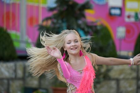 Photo for A young girl in pink is dancing. Smiling dancing. Dancing in the street. In the costume dancing - Royalty Free Image