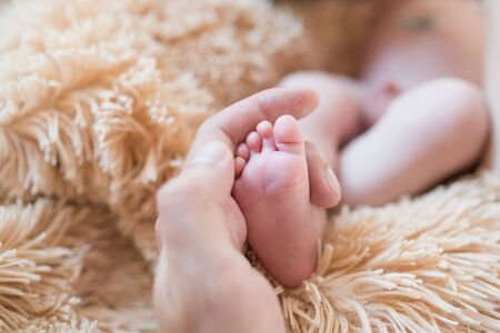 little foot in hand. Father holding the legs of a newborn in his hands. Mom cares for the baby after taking a bath. Parents to care for children. Children\'s health and happy family.
