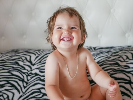 Foto de The naked baby is laughing. laugh in all your teeth. Happy laughing baby. White teeth of a newborn baby. Natural laugh. Carefree baby. - Imagen libre de derechos