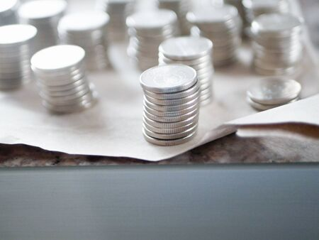 Photo pour Silver coins close up. Counting savings. Tax rate. Production costs. Distribution of finance. Laid out by a column. - image libre de droit