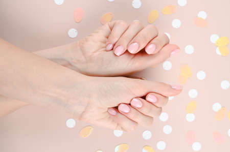 Photo pour Close up of female hands with pastel nail design. Pink nail polish manicured hands. Female hands on pink background with confetti. High quality photo - image libre de droit