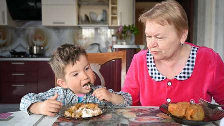 Photo pour grandmother feeds her grandson in the kitchen. - image libre de droit
