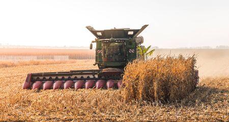Foto für Combine Harvester Machine Finishing Work on Agricultural Corn Field - Lizenzfreies Bild