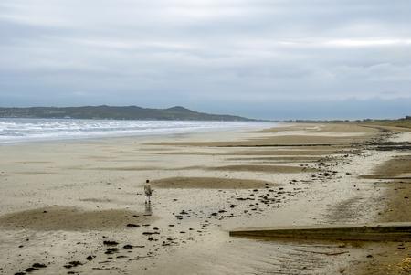 Dublin, Ireland, 25 October 2012: A Woman walking on Beach of Malahide