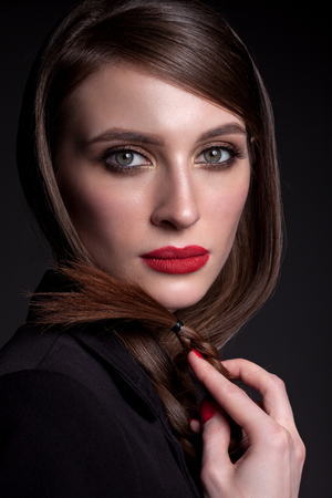 Portrait of a beautiful woman on a black background in a business style, with a beautiful make-up, in a black jacket.