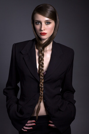 A beautiful woman in a black jacket and black pants, with a creative hairstyle on a gray background. In a strict erotic image.