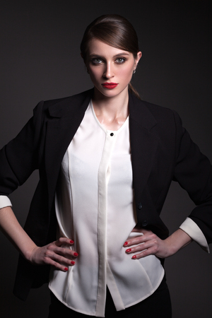 A beautiful woman in a black jacket and black pants, with a creative hairstyle on a gray background