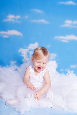 Beautiful baby girl with angel wings in white clothes posing on a background of the sky with clouds - decorated in the style of a little angel in the clouds