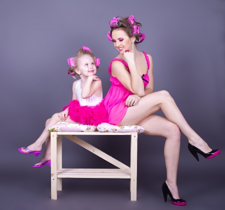 Photo pour A beautiful young mother with her daughter in the form of cheerful housewives  Studio shot on a gray background  Series - image libre de droit