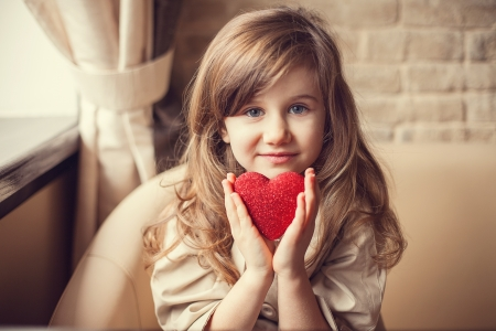 Photo pour Valentine Day - dreaming cute child with red Heart in hands.  - image libre de droit