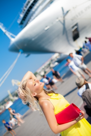 Beautiful Vacationing Woman in a dock, big cruise ship on background