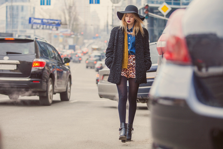 Photo for Fashionable young woman posing outside in a city street. Winter Fashion - Royalty Free Image